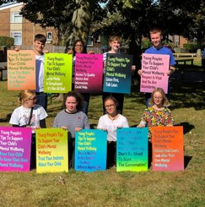 eight members of the Youth Cabinet sit or stand in two rows, holding multi-coloured posters showing their ten top tips
