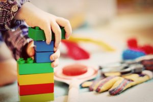 young child playing with green, blue, red and yellow blocks