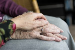 an older person has their hands on their knee and a second person lays their hand over the top to show support