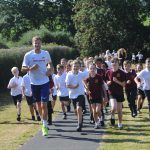 School health improvement grants - Eastbourne-based Olympic hurdler Seb Rodger leads children at Park Mead Primary School on the new track they use to run the 'Daily Mile'